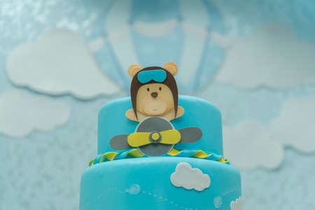 Close up of blue cake decorated with cute aviator bear, plane and clouds.