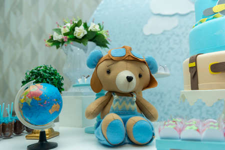 Teddy bear with aviator hat and glasses and a beautiful bouquet and blue and white balloons in the background. Bear with glasses and vintage airplane pilot helmet. Travel themed boy party decoration. Imagens