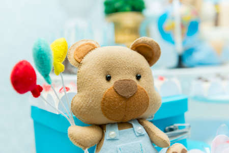 Boy party decoration with teddy bear holding colorful balloons next to luxurious blue ceramic vase with blurred background. Imagens