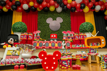 Florianopolis - Brazil. February 2, 2020: Birthday reception. Sweet table decorated with Mickey Mouse theme. Table with sweets, candies, dessert and cake.