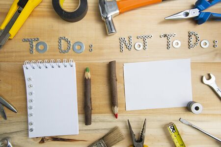"""Top view of the phrases """"to do"""" and """"not to do"""" made of nuts and washers on a wooden surface for planning the work. Construction tools framing wooden background shot from above."""