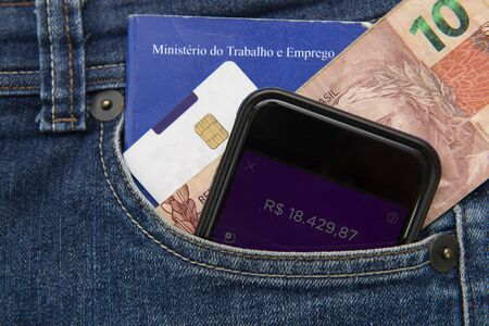 Close up of cell phone in pocket of pants with positive bank balance. Portfolio of work and social security. Real banknotes. Formal employment concept. Translate: Ministry of Labor and Employment.