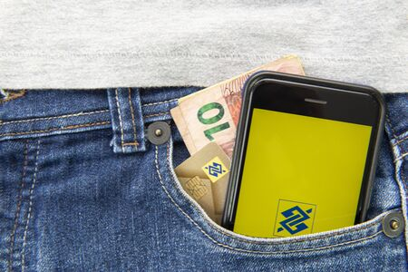 Florianopolis, Brazil, June 27, 2020: Close up of money, credit card and cell phone with screen on Brazil Bank (Banco do Brasil) app in pants pocket. The oldest bank in the Brazil. Imagens