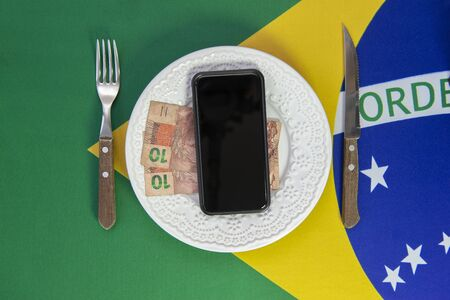 Top view of cellular over food plate next to cutlery and Brazilian flag in the background. Mobile phone with black screen.