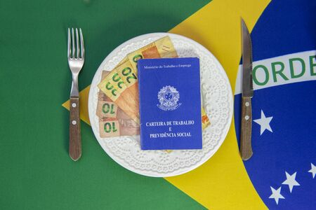 Top view of Brazilian work card on plate of food with cutlery beside it. Brazilian flag in the background. Translate: Digital work card. Concept for family support.