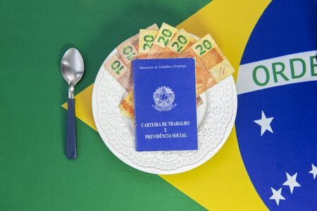 Top view of brazilian work card and money on plate of food, Background Brazilian flag. Translate: Ministry of Labor and Employment - Employment and Social Security document. Concept of family support