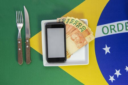 Top view of cellular over food plate next to cutlery and Brazilian flag in the background. Mobile phone with blank screen. Imagens