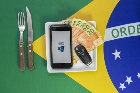 Top view of cellphone, money bills and car key on plate. Background Brazilian flag. Translate: National digital traffic card. Concept of family support with car. Imagens