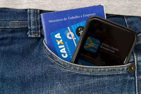 Florianopolis, Brazil. June 27, 2020: Close up of work and social security document, bank card, cash and cell phone application for emergency assistance. Economicand social crisis in Brazil. Editorial