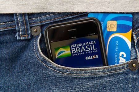 Florianopolis, Brasil - June 27, 2020: Close up of App and card in pocket. Translate: Brazil's beloved homeland - Federal Government - Caixa. Hello, welcome to: Federal Government Emergency Aid.