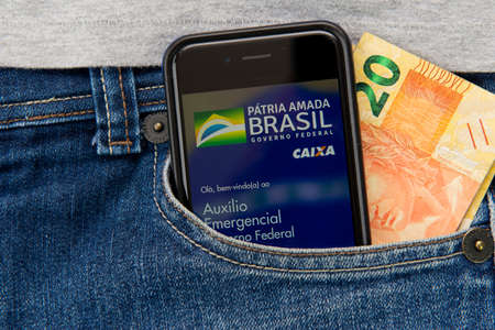 Florianopolis, Brasil - June 27, 2020: Close up of mobile and money in pocket. Translate: Brazil's beloved homeland - Federal Government - Caixa. Hello, welcome to: Federal Government Emergency Aid Editorial