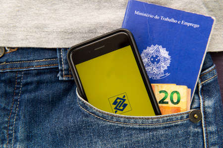 Florianopolis, Brazil. June 27, 2020: Close up of cellphone, Work brazilian card and cash in trouser pocket. Brazil Bank screen (Banco do Brasil). Translate: Ministry of Labor and Employment.