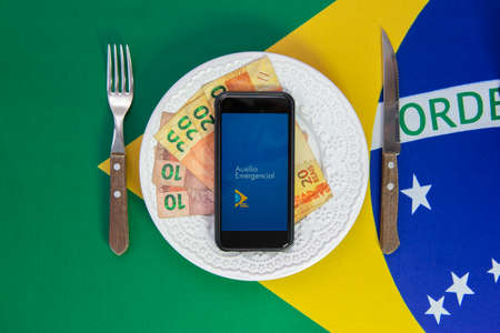Florianopolis, Brazil. June 27, 2020: Money and Cell Phone with the image of the Emergency Aid plan Brazilian dish of food. Concept of social aid to the neediest. Background Brazilian flag. Editorial