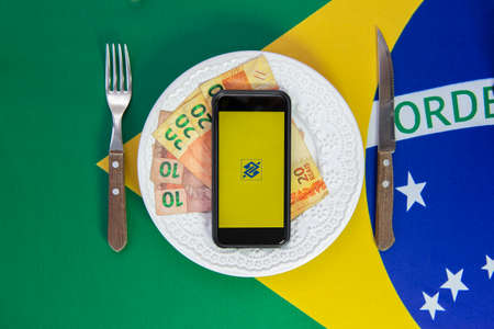 Florianopolis, Brazil June 27, 2020: Top view of cellular over food plate next to cutlery and Brazilian flag in the background. Mobile phone with Banco do Brasil application. Oldest Brazilian bank.