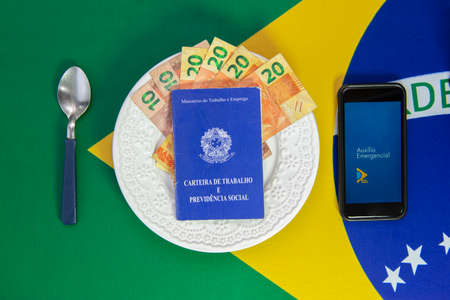 Florianopolis, Brazil. June 27, 2020: Money in Work Card and Cell Phone with the image of the Emergency Aid (Auxilio Emergencial) plan Brazilian dish of food. Concept of social aid to the neediest. Editorial