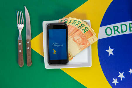 Florianopolis, Brazil. June 27, 2020: Money and Cell Phone with the image of the Emergency Aid (Auxilio Emergencial) plan Brazilian dish of food. Concept of social aid to the neediest.