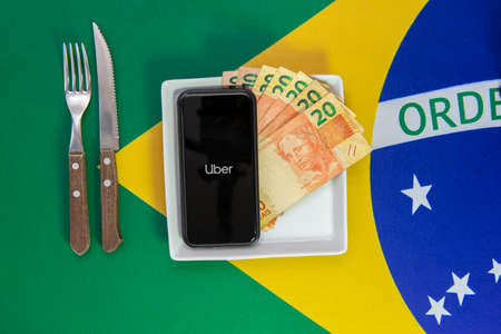 Florianopolis, Brazil June 27, 2020: Top view of cellular over food plate next to cutlery and Brazilian flag in the background. Mobile phone with Uber application. Family support for many Brazilians.