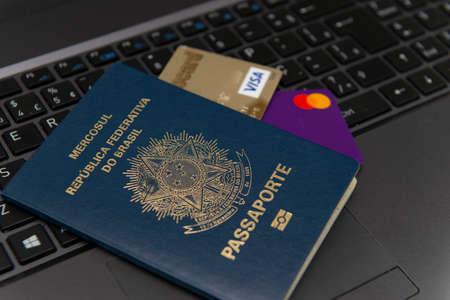 Florianopolis, Brazil. June 27, 2020: Close up Brazilian passport with credit cards inside on laptop keyboard. International travel expenses.