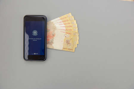 June 27, 2020, Brazil: Top View of cellphone and Real banknotes - Brazilian work document and social security document on white background (Carteira de Trabalho e Previdência Social). Copy space. Editorial