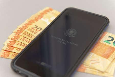 June 27, 2020, Brazil: Close up of cellphone and Real banknotes - Brazilian work document and social security document on white background (Carteira de Trabalho e Previdência Social). Editorial