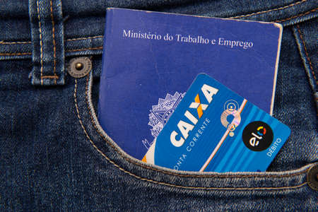 Close up of credit card and work and social security card (Carteira de trabalho). Formal employment concept. Translate: Ministry of Labor and Employment / Caixa - Checking account, debt.