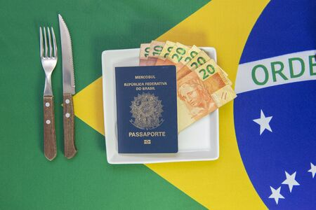 Brazilian passport with Real banknotes on a white plate with the flag of Brazil in the background. cutlery next to the plate.