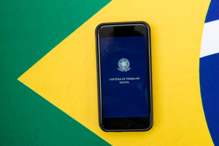 Florianopolis, Brazil, June 27, 2020: Top view digital work card on Brazilian flag. Concept of formal work and government benefits. Work and social security.