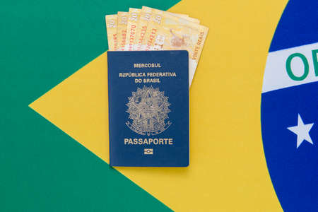 Top view of Brazilian passport and money bills inside on Brazilian flag in the background. Travel concept. Immigration and emigration, tourism and international travel.
