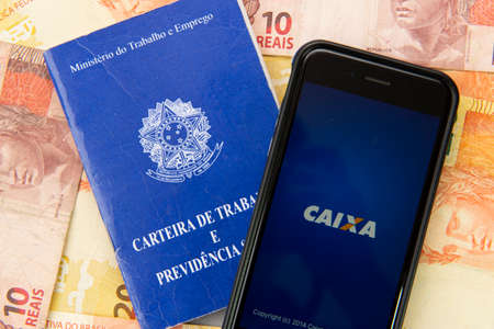 Florianopolis, Brazil. June 27, 2020: top view of Work Card and Mobile with Caixa Bank screen, main federal bank in Brazil on money bills. Caixa is the most popular Brazilian bank.