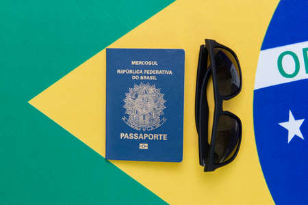 Top view of Brazilian passport and sunglasses on Brazilian flag in the background. Travel concept. Immigration and emigration, tourism and international travel.