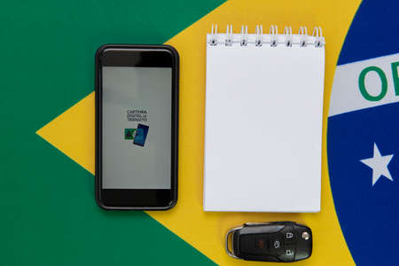 Florianopolis, Brazil. June 27, 2020: Top view of Cell Phone with Brazilian Digital Traffic Card (Digital Traffic Card) next to sunglasses, notepads, car keys, lucky data on the Brazilian flag.