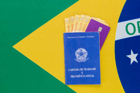 Top view of Brazilian passport with cash and credit card inside on Brazilian flag in the background. Travel concept. Immigration and emigration, tourism and international travel.
