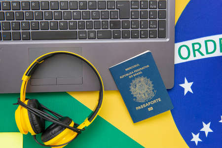 Top view of travel objects: Brazilian passport, yellow headphones and notebook on Brazilian flag in the background. Travel concept. Immigration and emigration, tourism and international travel. Imagens