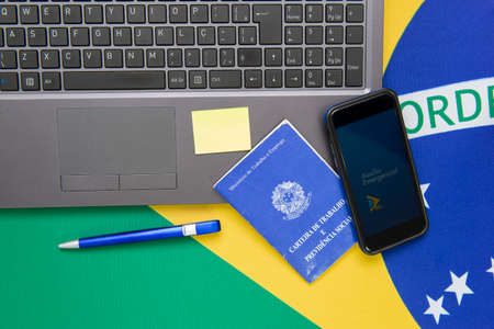 Florianopolis, Brazil, June 27, 2020: Top view of Cell phone with the Brazilian Emergency Aid application (Auxilio Emergencial) on notebook and national flag. Social and financial assistance. Editorial