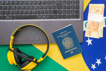 Top view of travel objects: Brazilian passport, notebook, sunglasses, keys, credit card, notepad, pen, money and Brazilian flag in the background. Travel concept.