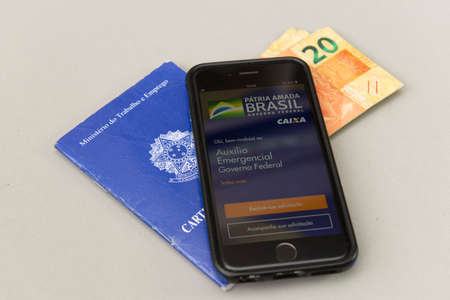 Florianopolis, Brazil, June 27, 2020: Top view of printed and digital work card on white background. Concept of formal work and government benefits. Work and social security. Editorial