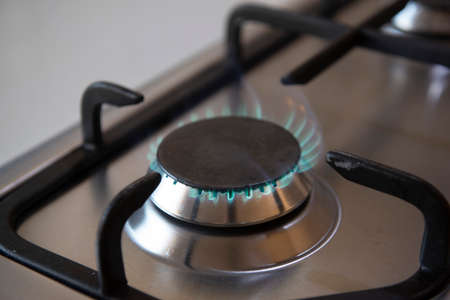 kitchen gas cooker with burning fire propane. Flame of a gas stove in stainless steel. Modern stove.
