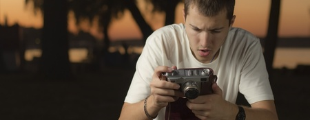 Young photographer setting up his old camera