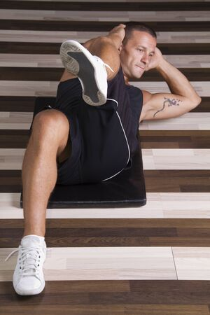 Young man doing abs exercise Stock Photo - 10706490