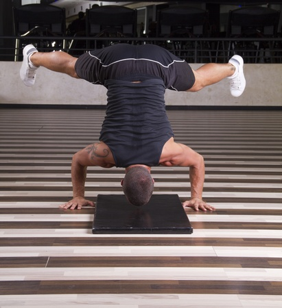 Fitness instructor doing stand on his head   Stock Photo - 10706484