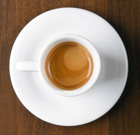 Espresso in white coffee cup, served in coffee&bar on wooden table Stock Photo