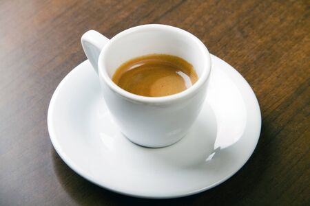 Coffee espresso served in white cup on wooden table, studio shoot Stock Photo