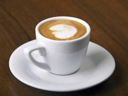 Coffee Macchiato directly above, served in white cup, on wooden table, studio shoot Stock Photo