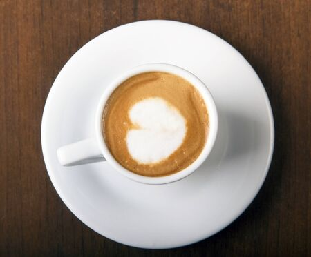 Coffee Macchiato directly above, served in white cup, on wooden table Stock Photo