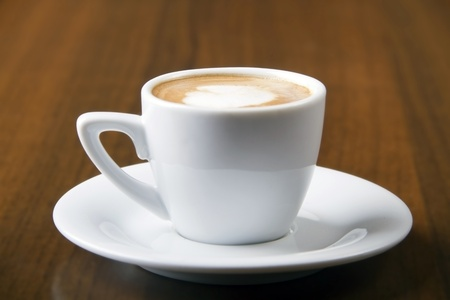 Macchiato coffe served in white cup on wooden table