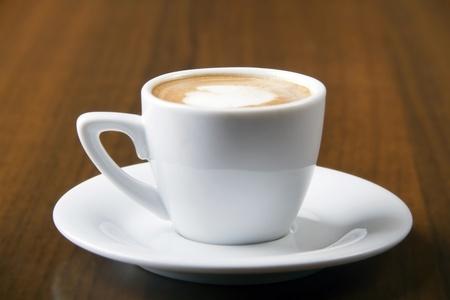 Macchiato Kaffee serviert in weißen Tasse auf Holztisch Lizenzfreie Bilder