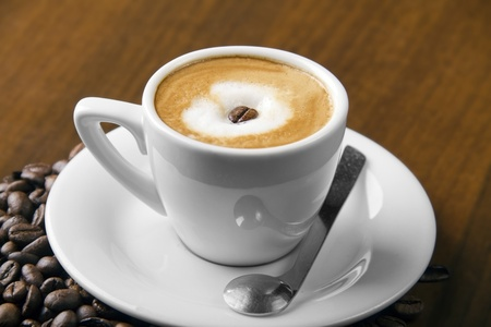 Macchiato coffe with espresso bean in center of steamed milk cream and surrounded with coffee beans