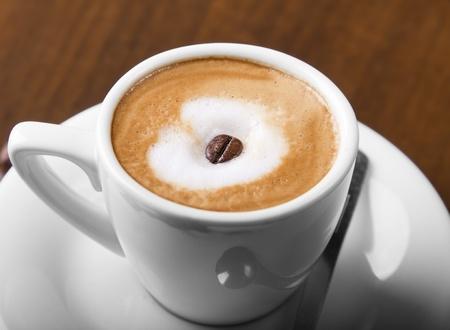 Macchiato coffe with espresso bean in center of steamed milk cream Stock Photo