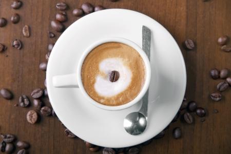Espresso macchiato in white cup, surrounded with espresso coffee beans Stock Photo