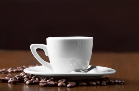 Espresso Coffee in white cup surrounded with coffee beans